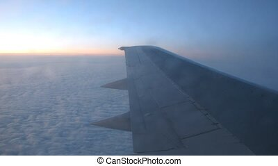 From window of flying plane is visible sunset and clouds