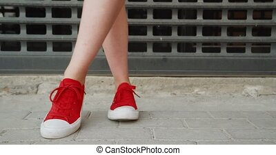 Front and side view of girl feet in red trainers