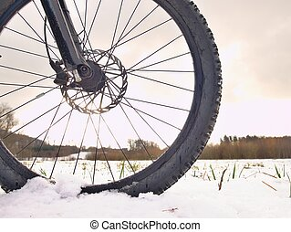 Front bike detail on a winter trail, path covered by snow. Sportive backgrounds