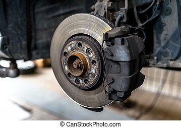 Front brake discs with caliper and brake pads in the car, on a car lift in a workshop.