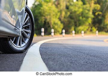Front car wheel on the asphalt road