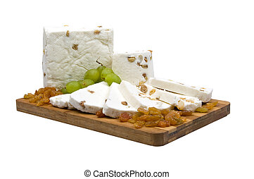 front close-up of a piece and slices of cheese with raisins and grapes , on a wooden cutting board, on a white background