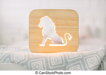 Front close up view of stylish wooden night lamp with lion cut out picture, on gray blanket at cozy light bedroom interior. Wooden decorations at home interior