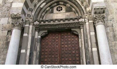 Front door of small medieval church in the old historic centre of Genoa, Italy, a UNESCO World Heritage Site