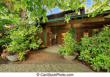 Front door of the cider house with shrubs in the front
