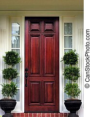 topiary plants at front door of home