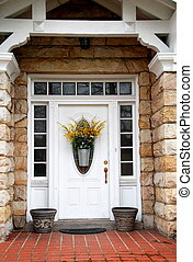 Front Door - White door with transom and side lights on...