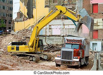 Front end loader putting debris from a demolished building into a dump truck.