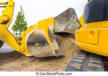 Front end loader dumping stone and sand in a mining quarry