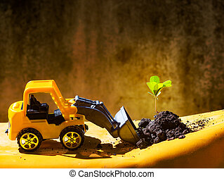 Front end loader truck toy scooping up green plant and earth on yellow ground