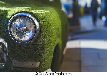 Front headlight of an old car in summer covered with artificial grass. Decorated on classical car