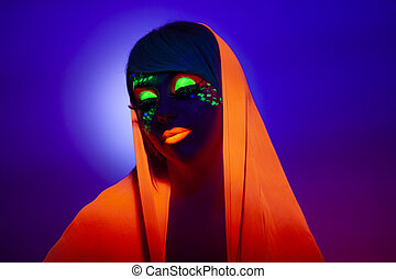 Front image of a woman with artistic makeup and orange scarf on her head, with closed eyes, over purple background.