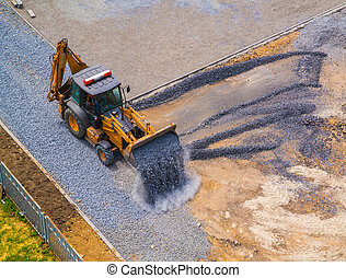 Front loader poured gravel from the ladle at the construction site of the school stadium