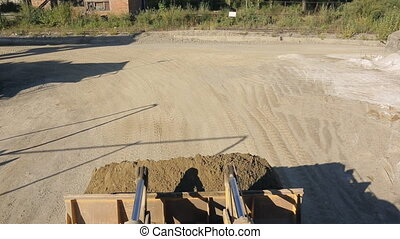 Front loader rides plant and discharges the sand in the...
