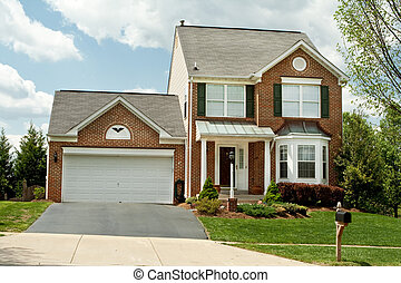 Front of a new brick style single family home in suburban Maryland, USA. Very small house for such a new building.