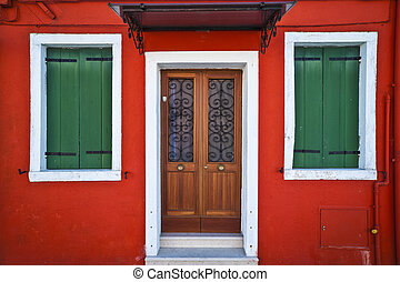Front of a red house in Burano, Italy