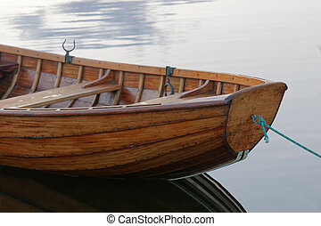 Front of a rowboat in calm water