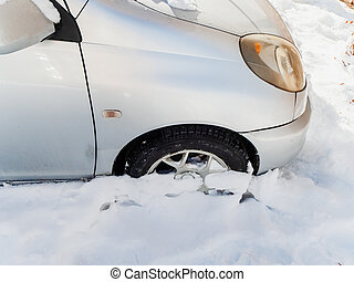 Front of a silver car stuck in a snowdrift