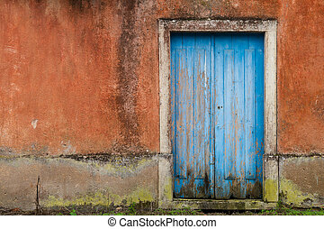 Front of abandoned house with blue door