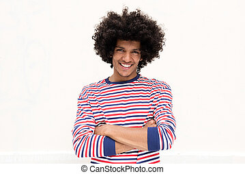Front of smiling young african american man with afro hair and arms crossed against isolated white background