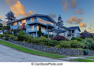 Front of the large blue house with sunset clouds.