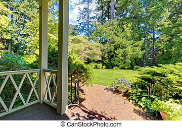 Front porch house exterior with summer garden.