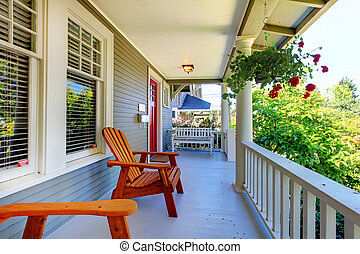 Front porch of the grey house with white railings and two windows with flowers