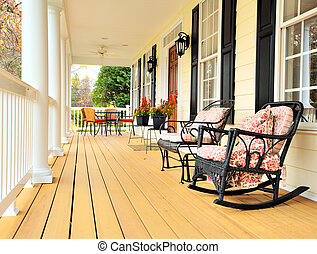 Low angle view of a large front porch with furniture and potted plants. Vertical format.