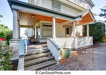 Front porch with chairs and columns of craftsman home.
