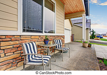 Front Porch with sittting arrangement in classic wooden home.