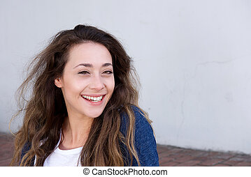young woman sitting outside laughing