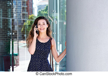 young woman talking on cell phone outside