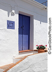 front side of typical spanish house with beautiful blue wooden door