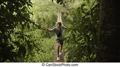 Front static view of a man walking across a shaky rope jungle bridge in the rain. Young man hanging to the sides of an unstable bridge. 4K