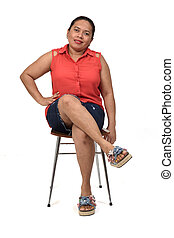 front view a woman sitting on a chair with the body in profile and looking at the camera on white background,legs crosse