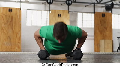 Front view athletic Caucasian man lifting alternate weights...