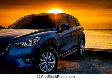 Front view blue compact SUV car with sport and modern design parked on concrete road by the sea at sunset. Electric car technology and business. Hybrid auto and automotive. Tropical road trip travel.