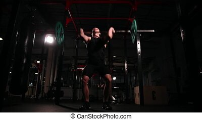 Front view camera moves on stedicam. A man in a black T-shirt comes up to the staff and begins to perform exercises from weightlifting.