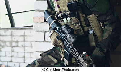 Front view close up of caucasian soldier with a rifle stand guard securing territory looking around.