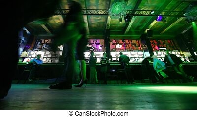 Front view from floor on some people sitting and relaxing at bar in nightclub