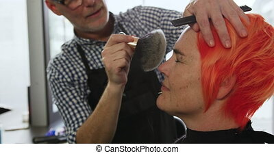 Alternative cool hair salon. Side view of a Caucasian male hairdresser working in a hair salon, brushing off cut hair with a brush from a Caucasian female client face, in slow motion