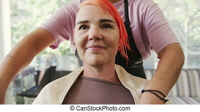 Front view hairdresser putting protection around woman neck...
