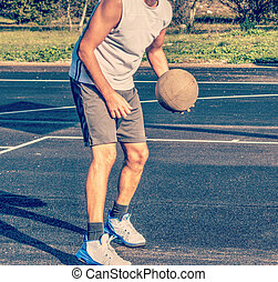 Front view of a basketball player holding a ball in a playground
