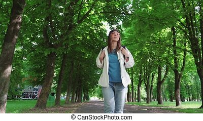 Front view of a beautiful woman in cap walking in the park ...