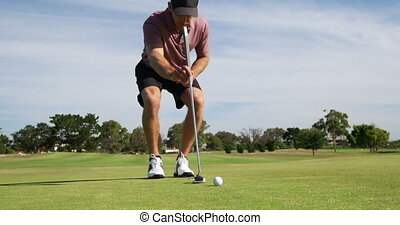Caucasian male golfer kneeling on a golf course on a sunny ...