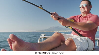 Front view of a Caucasian man fishing on boat - Front view ...