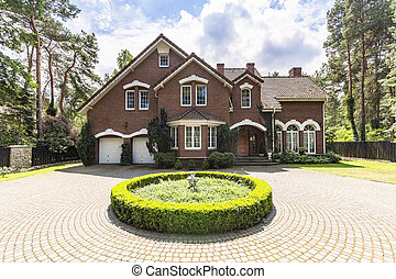 Front view of a driveway with a round garden and big, english style house in the background. Real photo