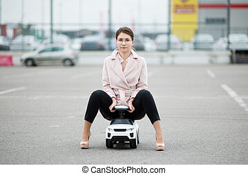 front view of a handsome young woman sitting in a child car in a parking lot