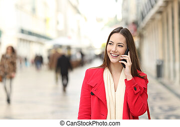 Front view of a happy woman talking on phone in winter