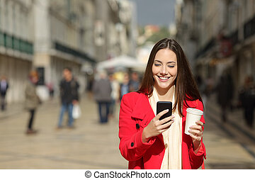 Front view of a happy woman using phone in winter